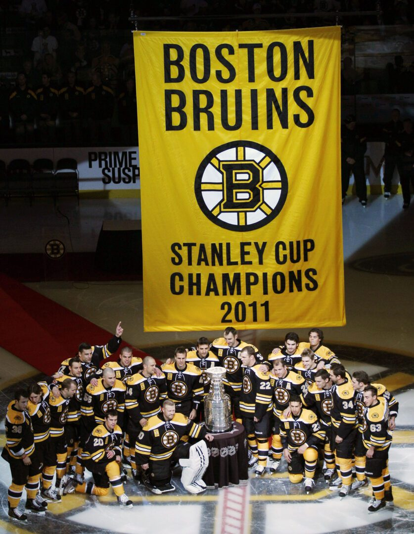 Boston Bruins players pose with the Stanley Cup and championship banner prior to facing the Philadelphia Flyers on opening night in an NHL hockey game in Boston, Thursday, Oct. 6, 2011. (AP Photo/Charles Krupa)