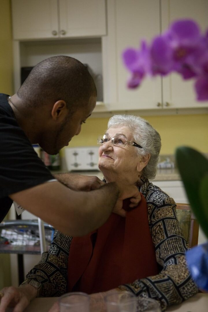File photo by Rupert Whiteley Nursing assistant Vincent White, left, helps Village House resident Carolina Vincent prepare for a meal.