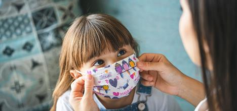 mother-putting-on-medical-mask-on-daughter
